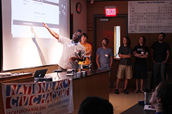 Gyepi Sam explains the team's code to the Hack for Western Mass participants at the end of the weekend.