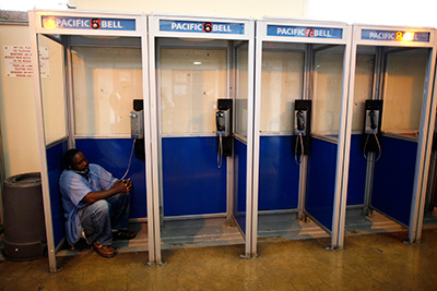 image of an incarcerated man at San Quentin prison crouching down in a phone booth on the phone